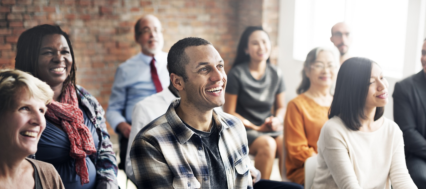 Image shows a diverse group of people looking towards someone talking to them. They are all smiling.