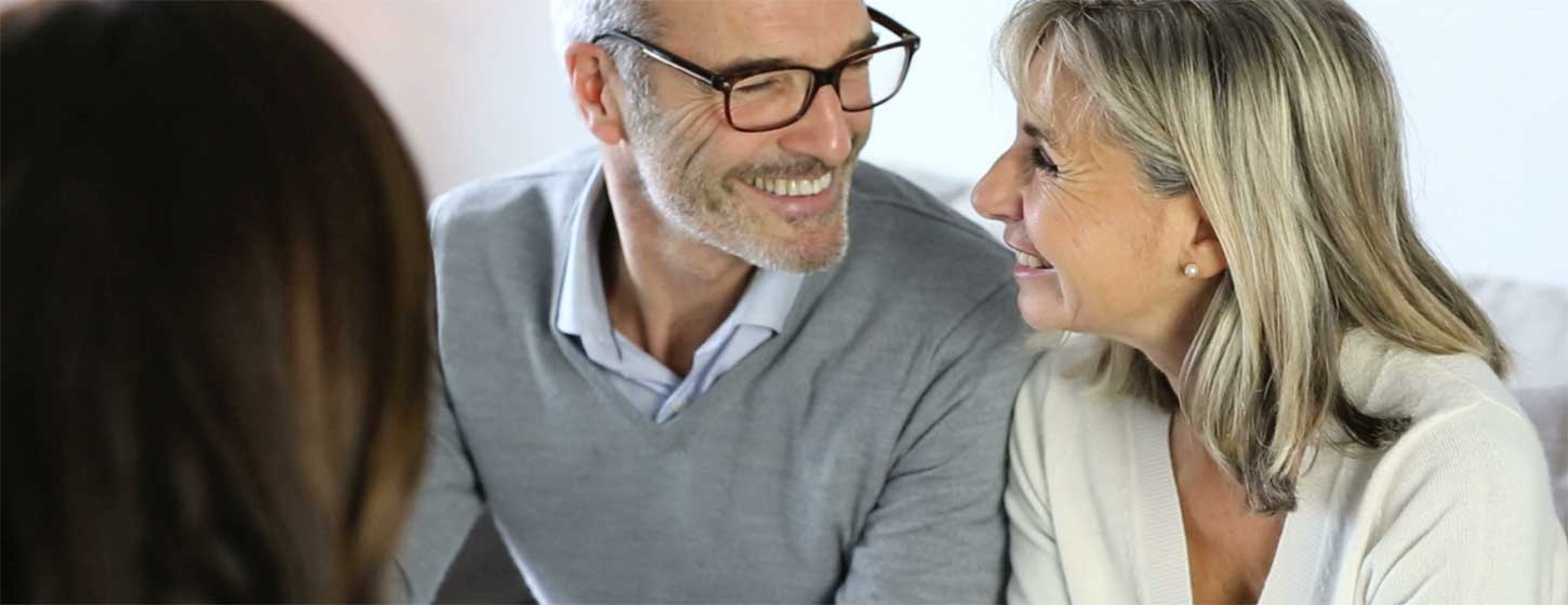 Older couple smiling at one another whilst getting financial advice.