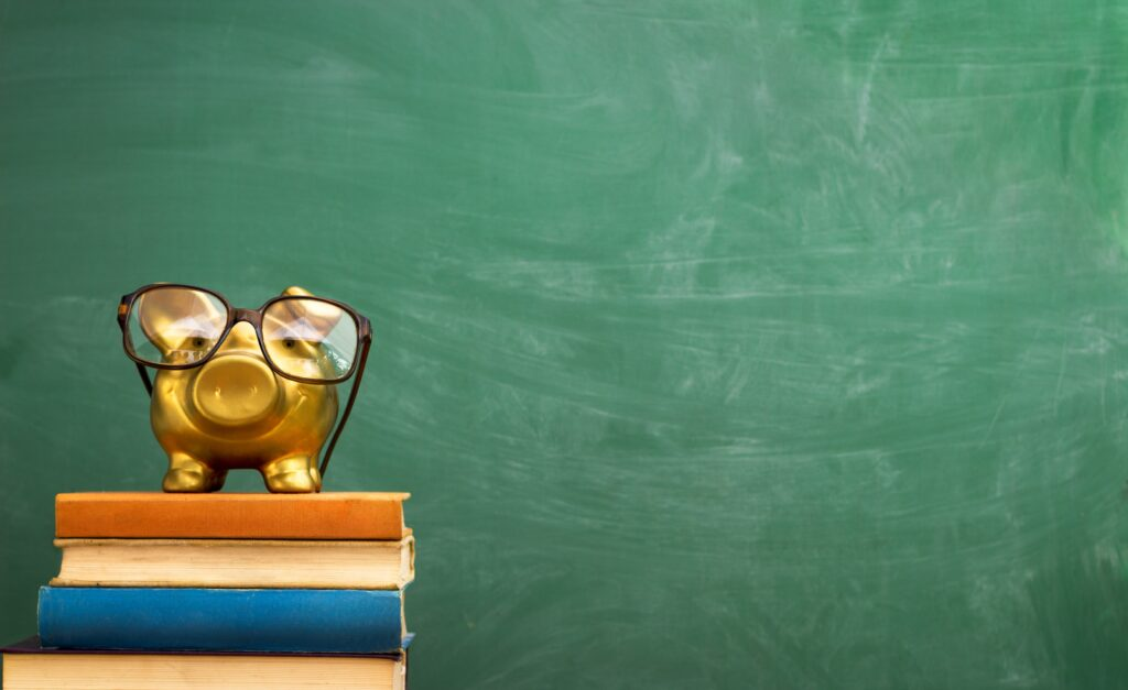 Piggy,Bank,With,Glasses,On,Books,,Education,Concept