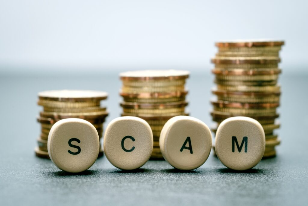 Scam,Letter,Block,And,Stack,Coins,,Business,Concept.