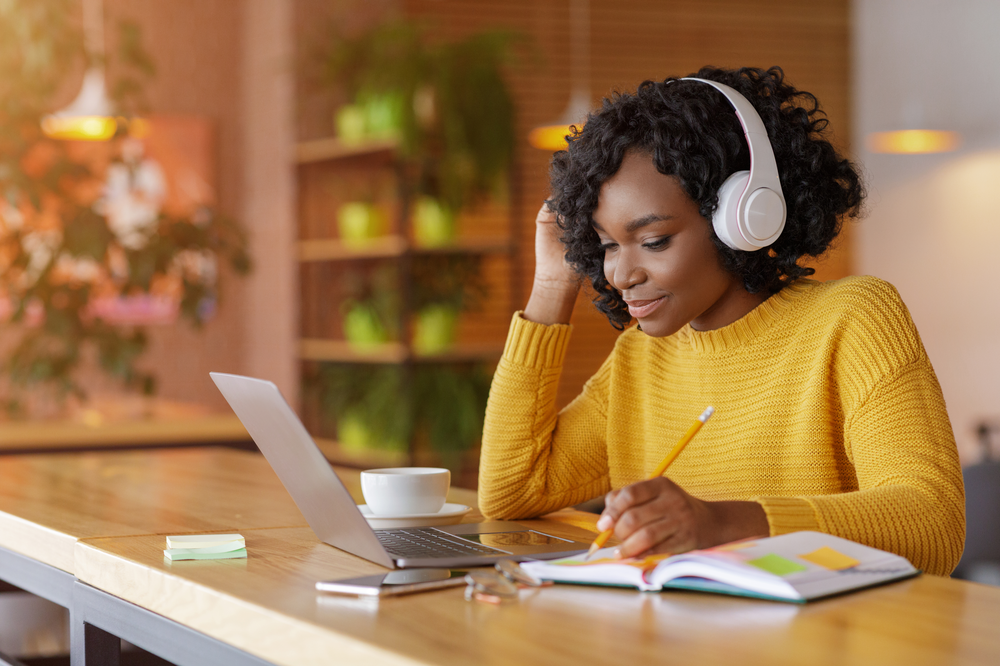 Woman in yellow jumper wearing headphones flip